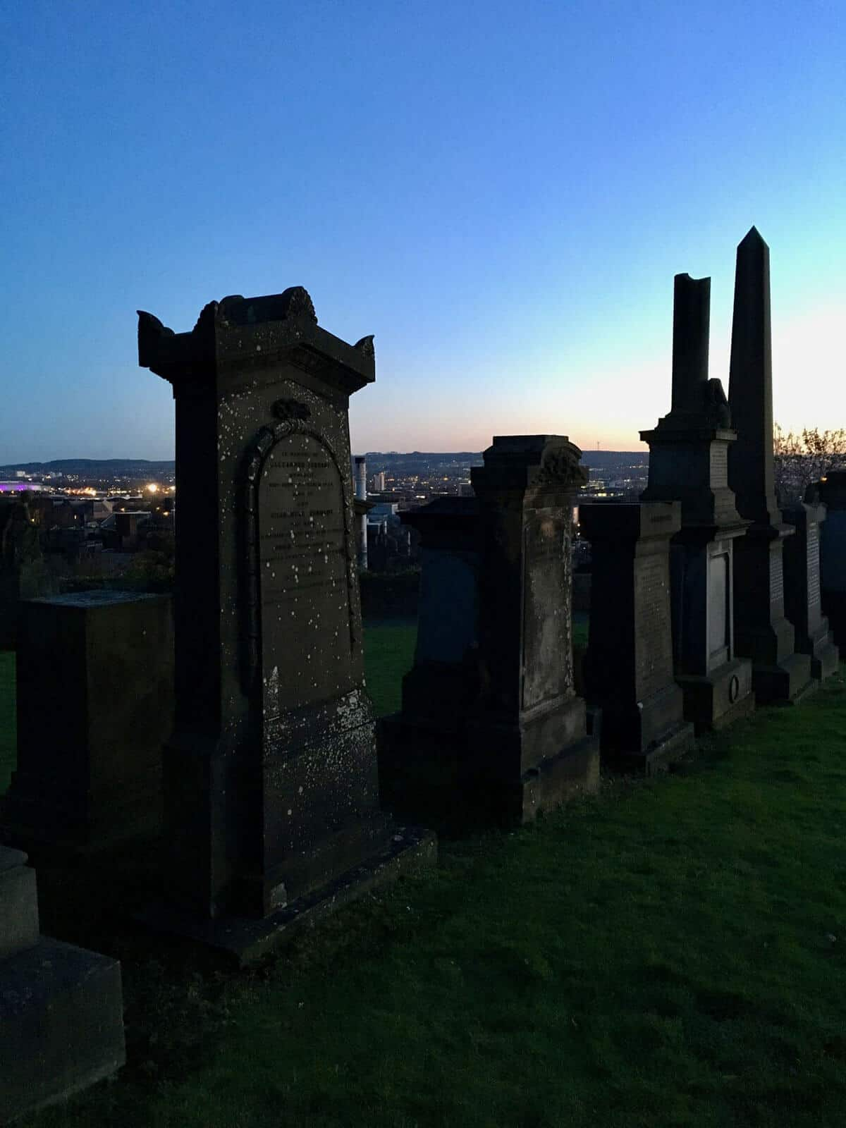 Six aged, mossy and weathered Victorian style grave stones and tombs with the Glasgow skyline in the back ground as the sun sets casting a dark shadow glow on the graves.