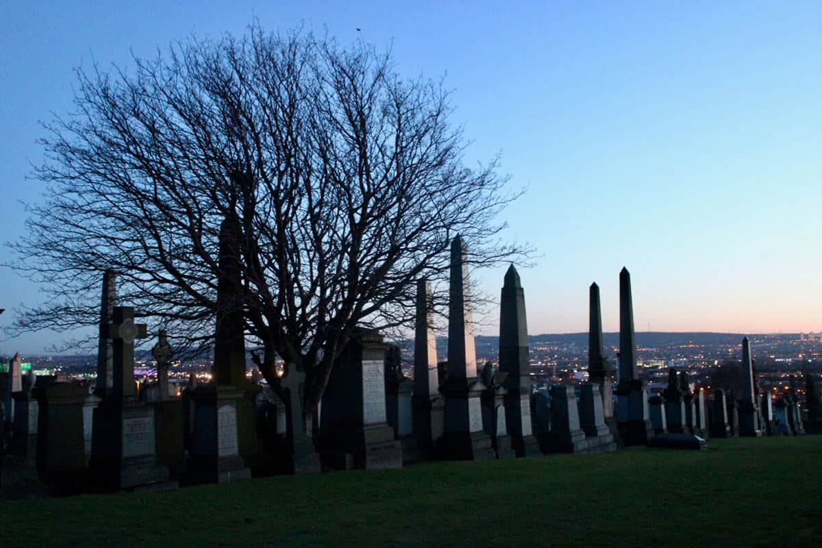 A green hill lined with several graves, cemetery stones and tombstones with a deciduous tree with no leaves sits behind the graves. The sun is setting and a red glow lights up the gravestones in the Glasgow Necropolis