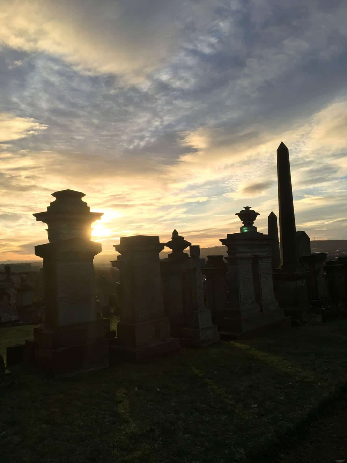 The sun rises with a calm yellow and blue cloud filled sky with the silhouette of several gravestones lined up next to each other in front of the Sunrise at Glasgow Necropolis