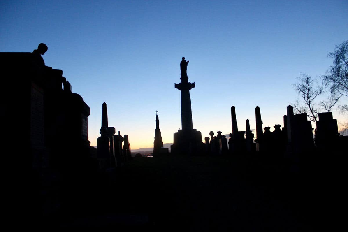 Victorian Graves in black shadows as the sun sets behind with an orange glow and a dark blue sky in the Glasgow Necropolis