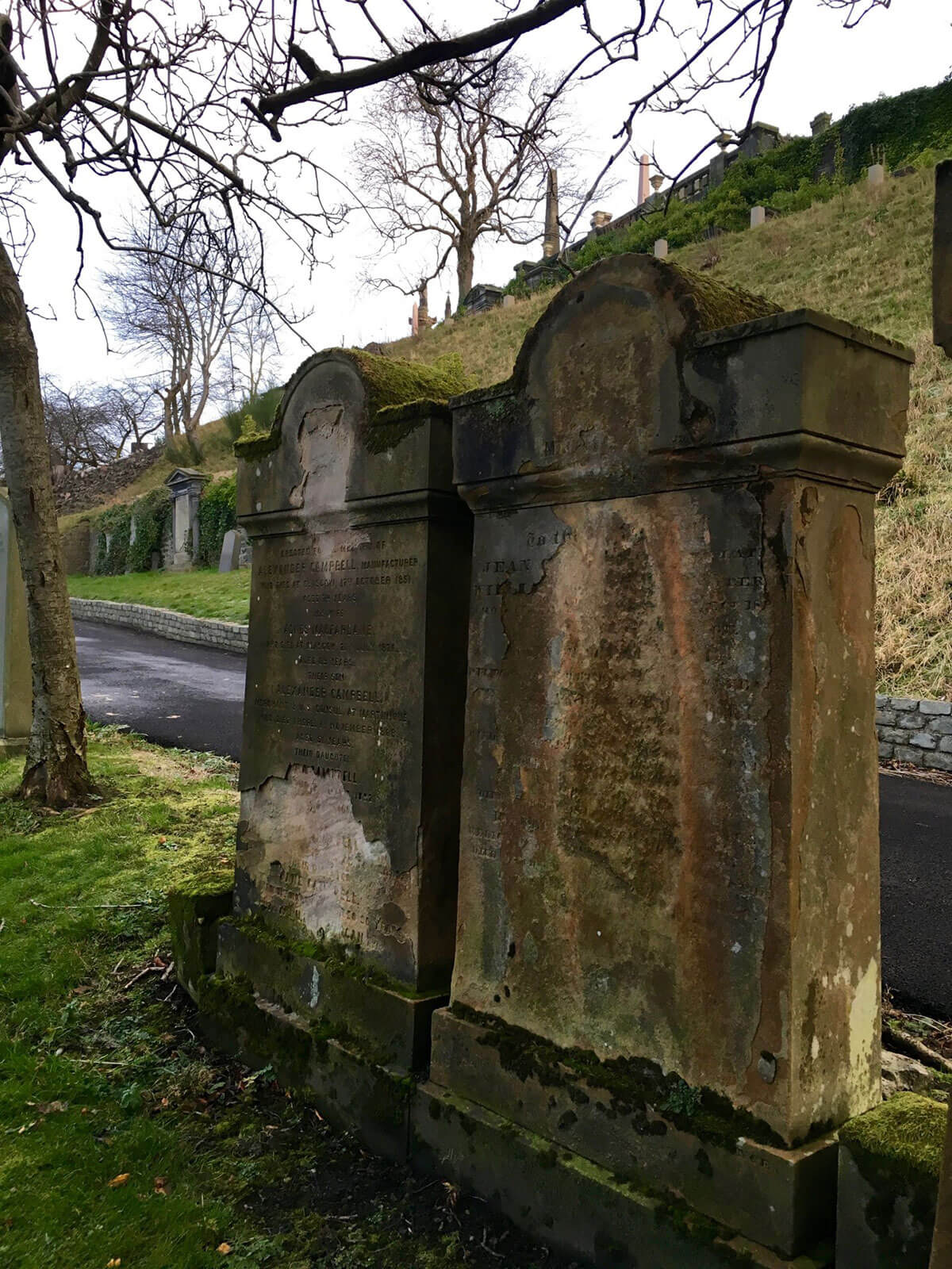 Two mossy graves that are weathered, aged and hard to read in Glasgow Necropolis. Overcast sky with more graves and tombstones and autumn trees with no leaves behind the two graves that sit next to each other.