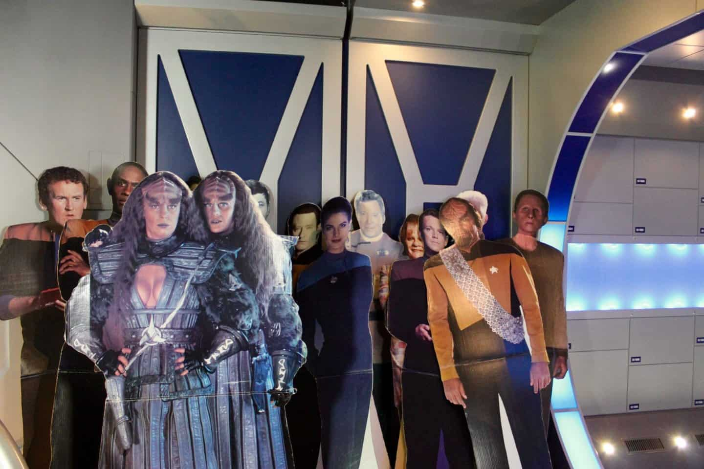 20 Star Trek Cardboard Cutouts in Vulcan Alberta of various characters from several different Star Trek series such as Worf and Data. All cardboard cutouts are standing up an leaning against two sliding doors with blue panels and white lined design mimicking a star trek ship interior.