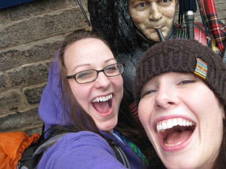 Two woman happily pose in front of a statue of a Scottish Bag Pipe Player in Edinburgh