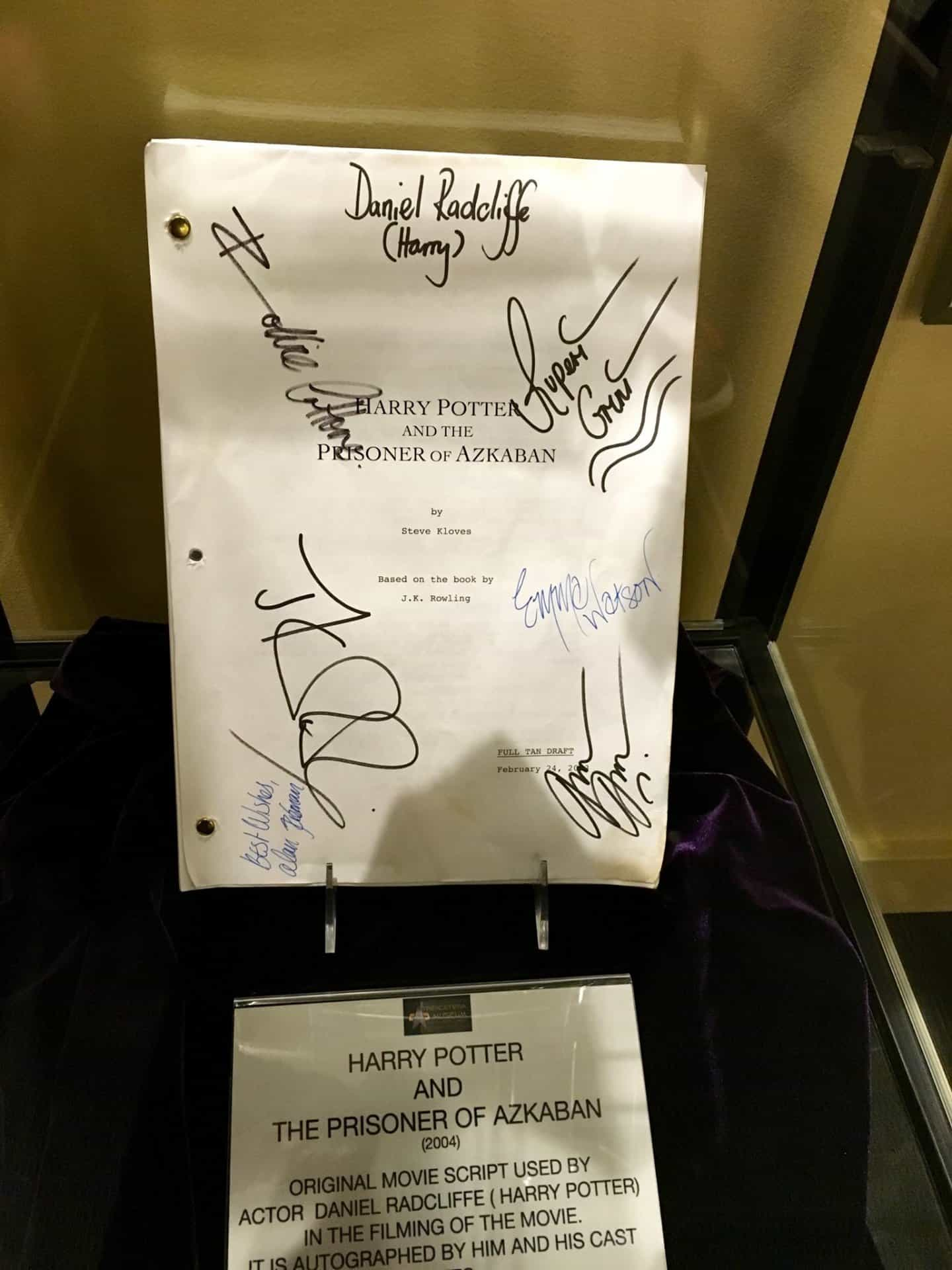 Autographed Harry Potter Script sits propped up in a glass case.