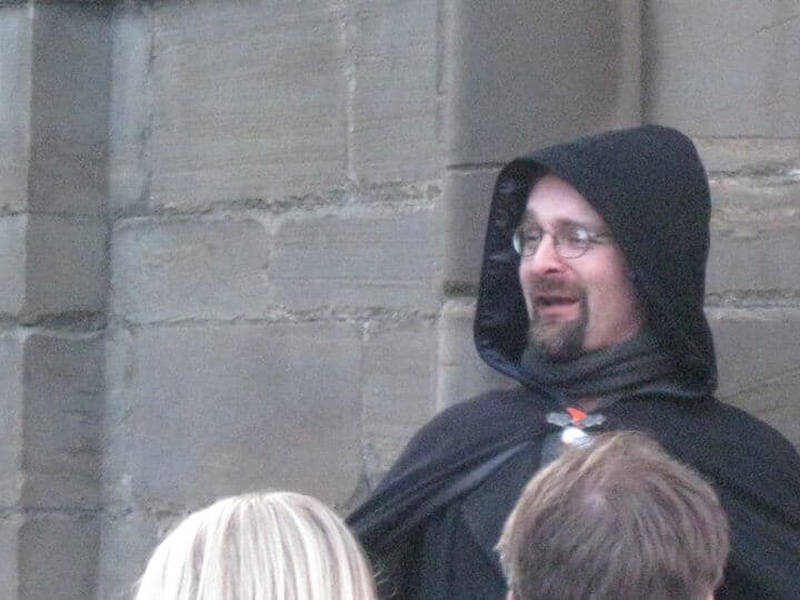 A man with a brown beard and glasses stands in a black hooded cloak. He stands in front of a concrete wall speaking to a group of people on a ghost tour.