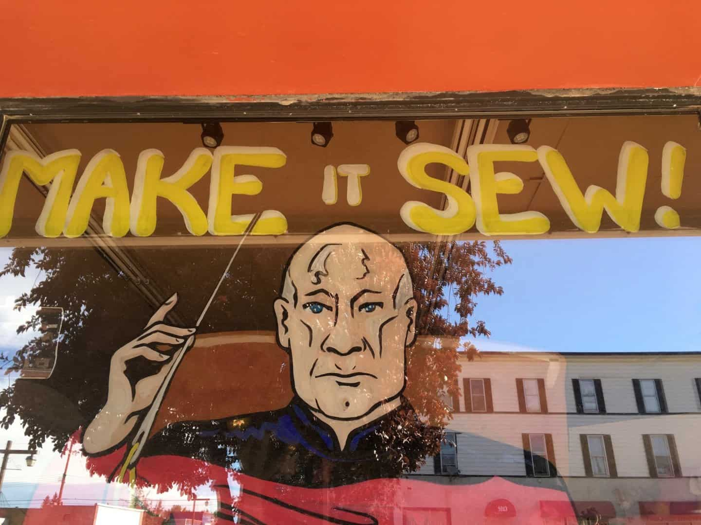 A glass window with a mural of Captain Picard holding a large sewing needle with the words Make it Sew above his head painted on the window.