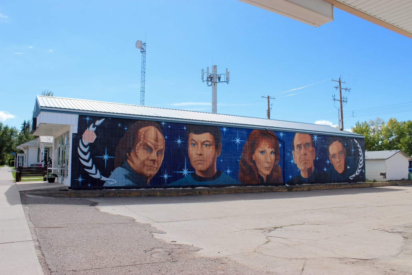 The side of a building with five staff members from the medical staff from various Star Trek series. Their heads are painted on side by side with a blue starry sky in the background.