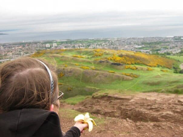 Girl sitting with banana looking out at Edinburgh from the top of Arthurs Seat. Green and yellow hills.