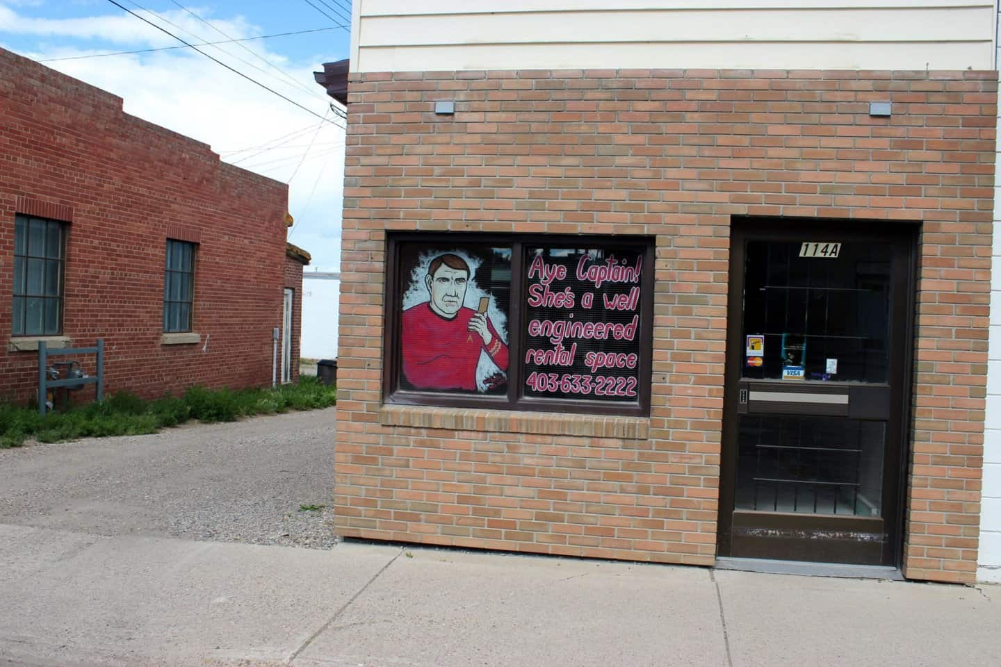 A brick building with a glass door on the right and a window on the left. The window has an art mural of a character from Star Trek - Scotty advertising that the window can be used as advertising space.