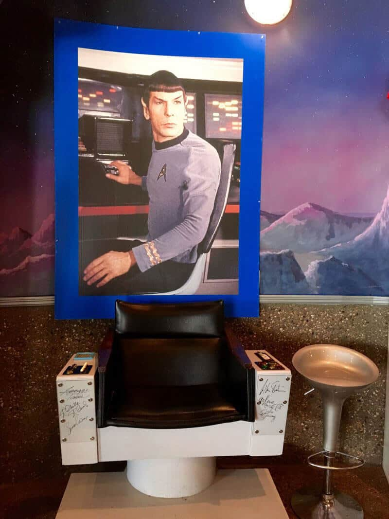 Located in the Vulcan Trek Center in Vulcan Alberta. Large photo of Spock from Star Trek sitting on his captains chair hanging on the wall above an autographed replica of the captains chair from the Star Trek series starring Spock. The chair is in the center of the photo with a white base and a black leather chair. The white base has autographs form various actors from Star Trek down the sides.