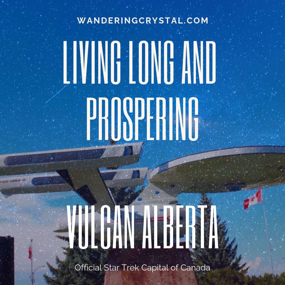 Vulcan Alberta Enterprise Ship on the side of the road on a stand in the blue sky is a giant replica of the Enterprise ship from Star Trek. Grey ship with a round flat front and two wings in the back of the ship.