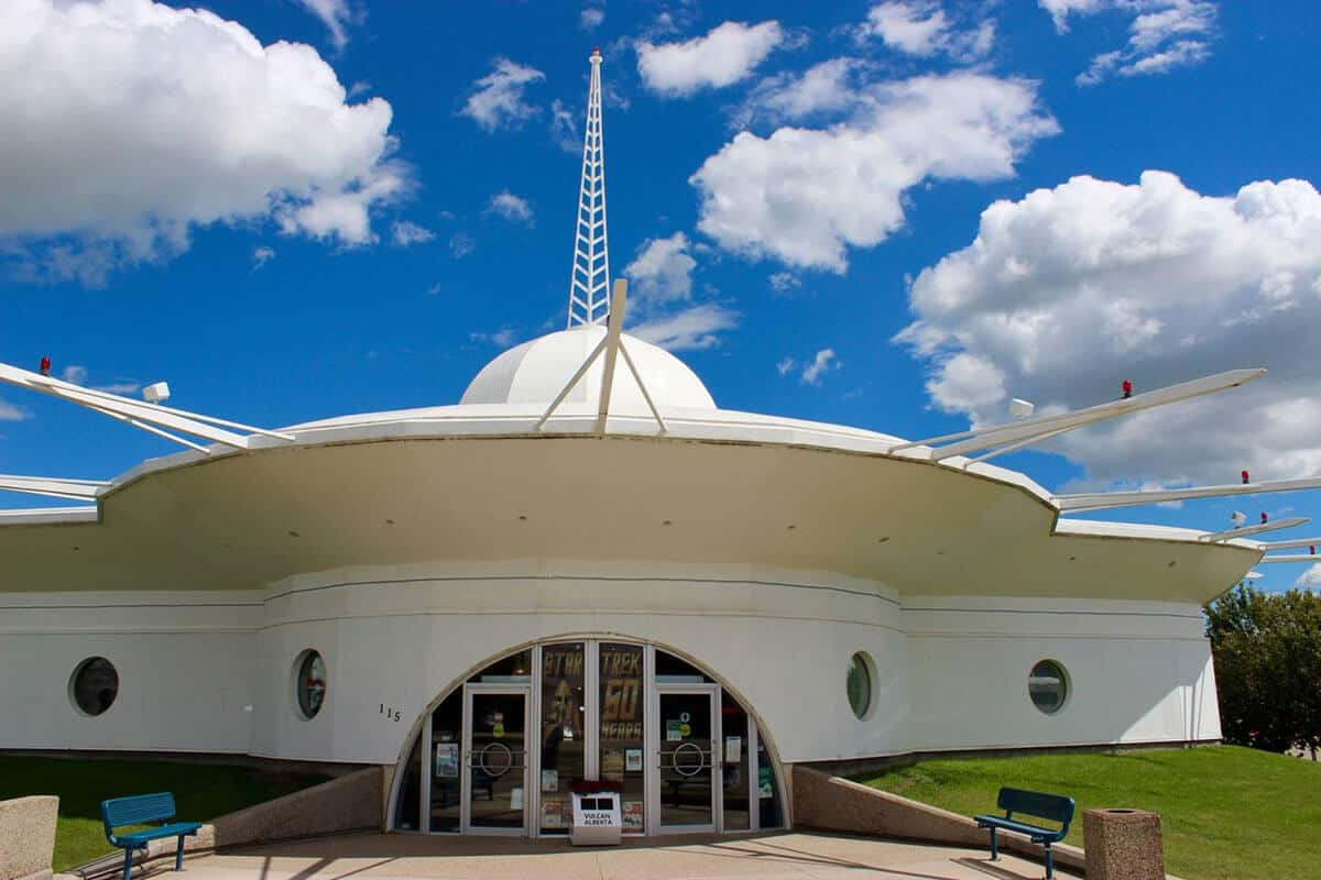 A white building shaped like a landing space ship on a bright sunny day. Blue sky with white puffy clouds in behind the building. The white building has circle windows and a large half circle glass door leading into the space ship like building. The building has a circular roof with a white dome and white metal rods sticking straight out from the circle part of the roof. Located in Vulcan Alberta the Star Trek capital of Canada.