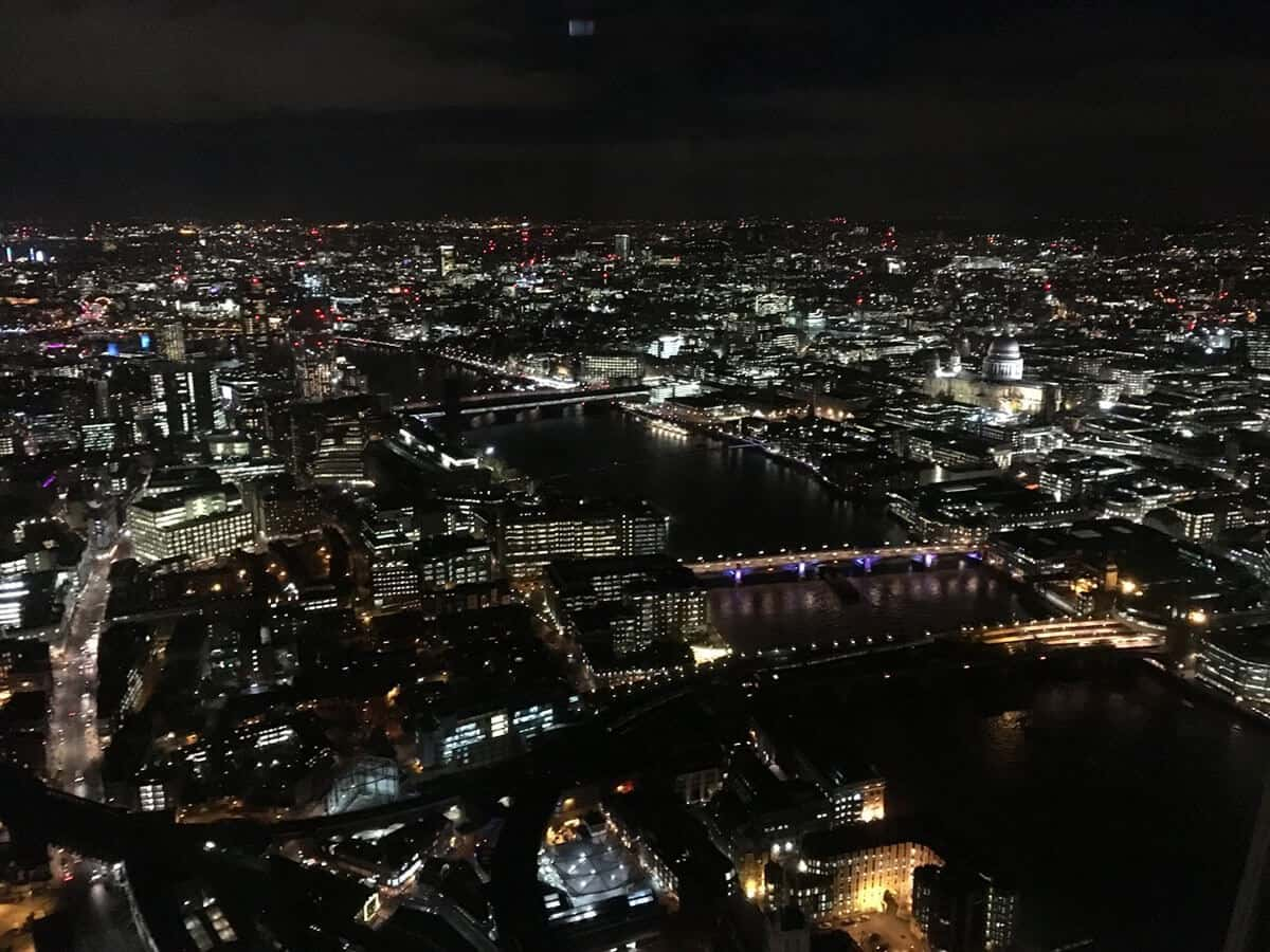 Panoramic view of the London sky line including the River Thames at night from the Shard. All of the buildings have lights on and are illuminating the dark sky.