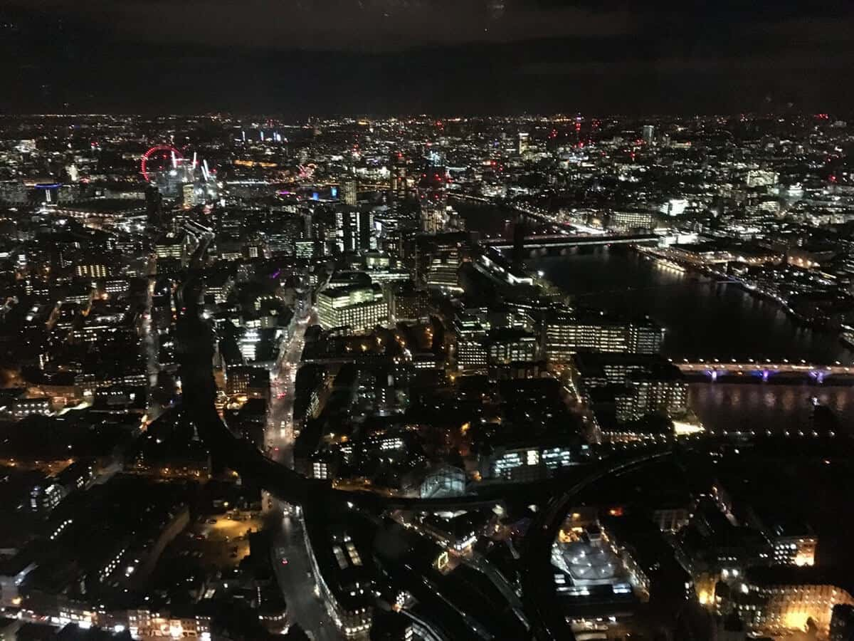 London Skyline from above with the dark night sky with the city of London lit up. Red ferris wheel is in the distance on the left side.