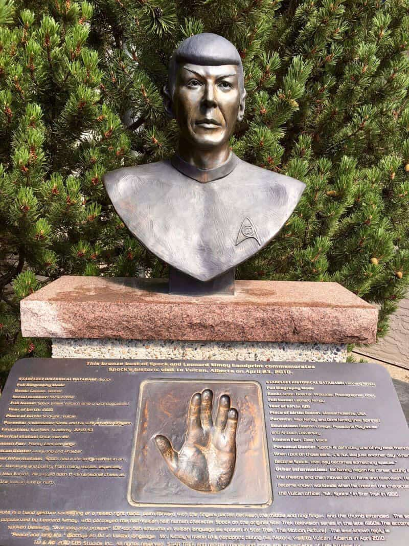 Bronze bust of Leonard Nimoy as Spock sitting on top of a concrete slab with a hand print of actor Leonard Nimoys hand in bronze on a plaque below the bust. A bushy green tree sits behind the bust of Spock.