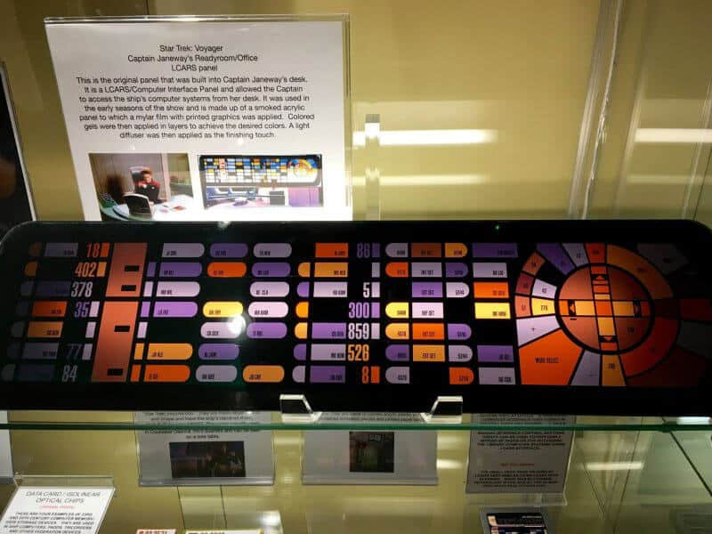 Behind a glass window sits an actual Star Trek Panel lit up with several rectangle pill shaped buttons. Actual panel from the Next Generation Star Trek series.