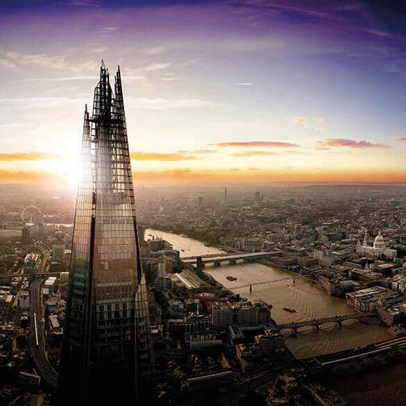 The Shard is in the left of the picture towering over London and the River Thames at dusk with an orange blue and purple sky. The Shard is made of glass with shard like tips at the top of the building.