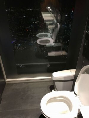 A view of the bathroom in the Shard. The toilet overlooks a window with the dark sky and lit up buildings from London city below.