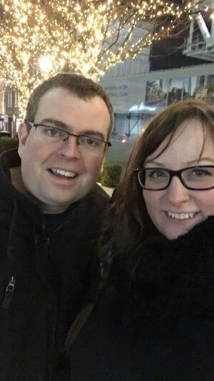 Man with brown hair dressed in black with glasses on the left and woman in black with glasses and brown hair on the right are posing in a cold London in front of trees that are full of bright white lights