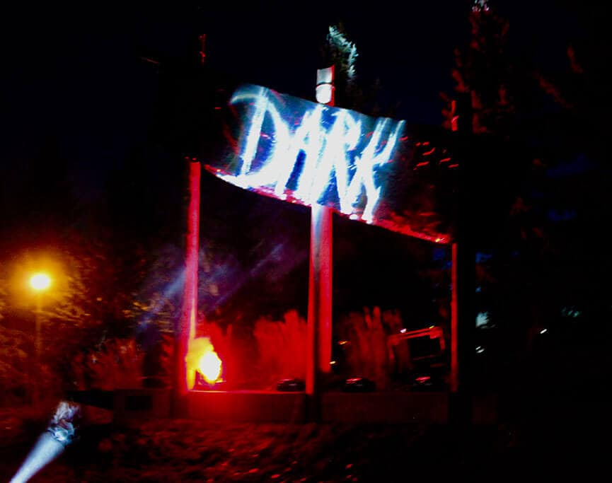 Entrance to Fort Edmonton Park, Red and yellow lights shine onto a sign that says DARK in white writing. Fog machine with red lights.
