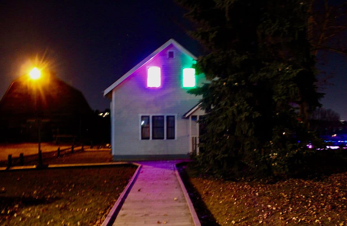 Outside night time path to a old white house with purple and green lights coming from the upstairs windows of the house.