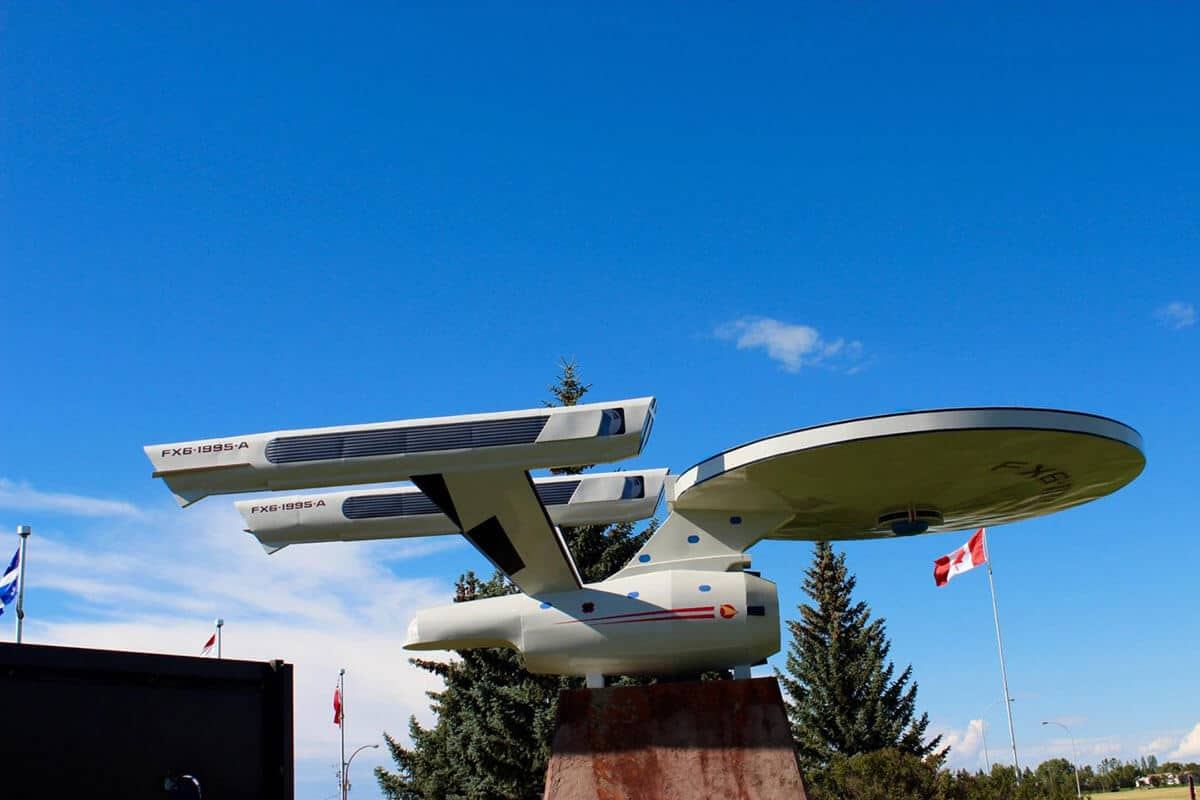 Giant roadside attraction in Vulcan Alberta is the Star Trek Enterprise Replica sitting on a concrete slab with the Canadian Flag flying behind it with an incredibly blue bright sky on a sunny day.