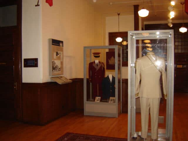 Inside McKay Avenue School & Edmonton Public Schools Archive and Museum stands two glass cases with a red military style suit in the left case and a white suit in the right case. The glass case with the white suit shows a ghost like reflection of a man.