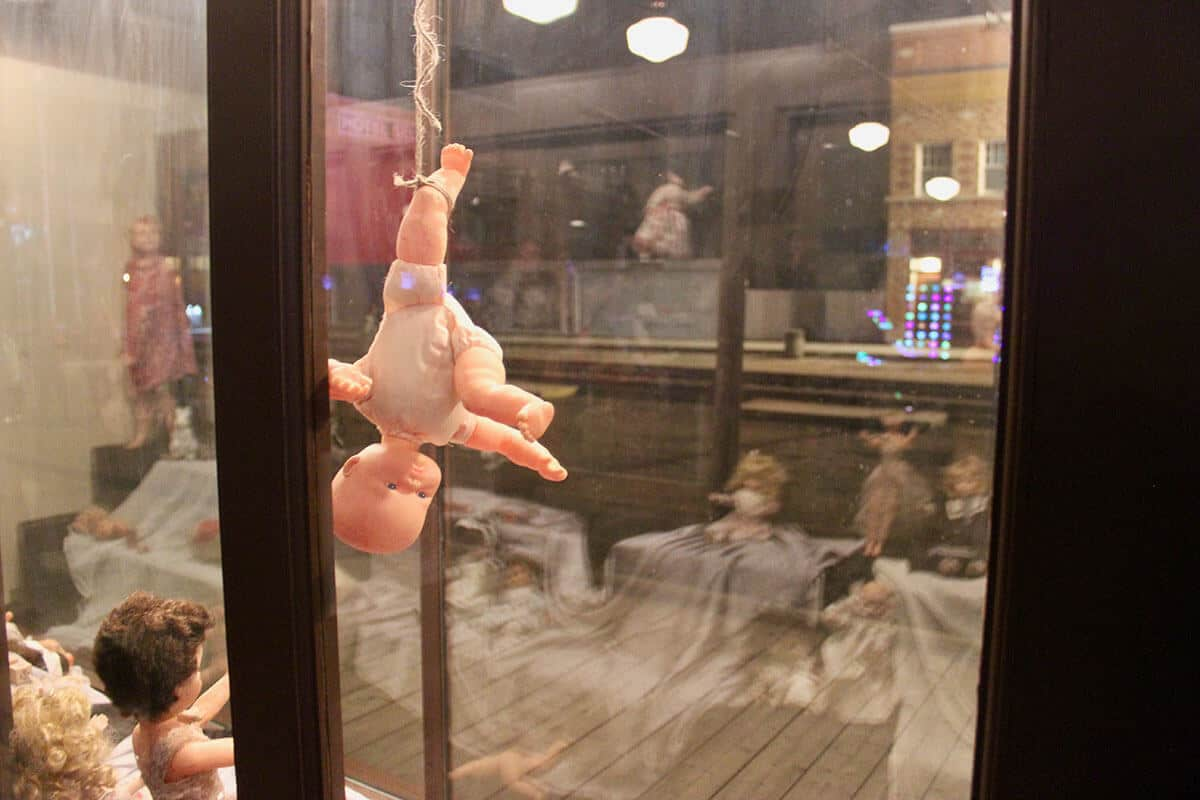 Baby Doll hanging upside down by foot on a rope in a window display at Fort Edmonton Park.