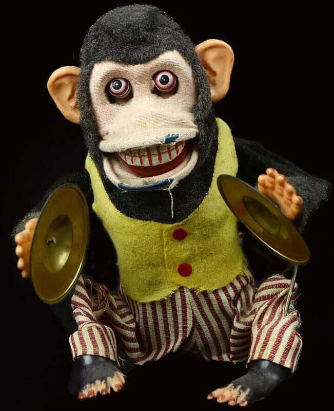 A creepy stuffed toy monkey that is aged and falling apart. His eyes are popping out of his head an he has an open toothed smile. He is wearing white and red striped pants with a yellow vest. The monkey is brown and is holding musical cymbals in each hand.