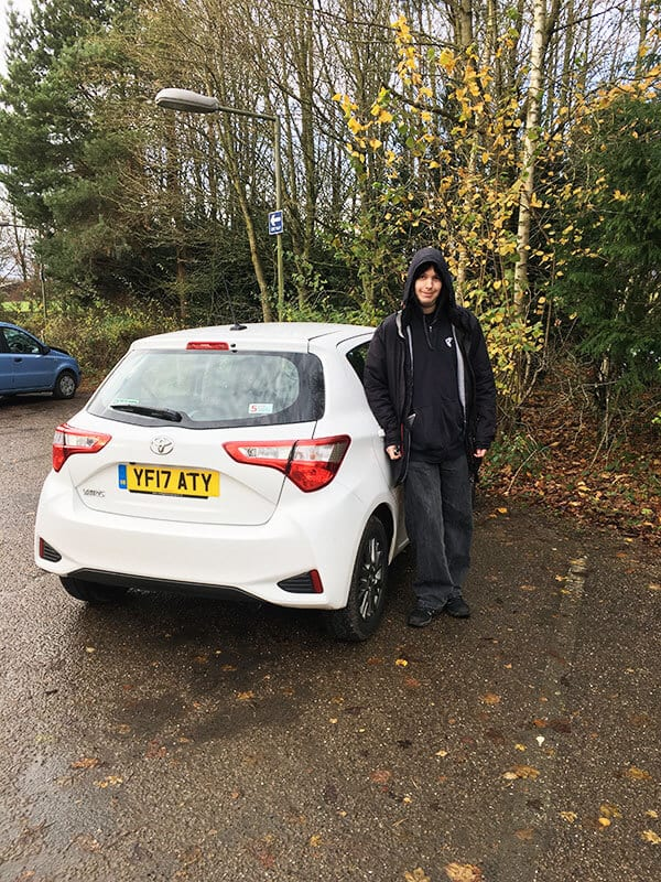 a man standing next to a small white toyota yaris in a car park. This tiny car was how we travelled through England on a terrifying journey.