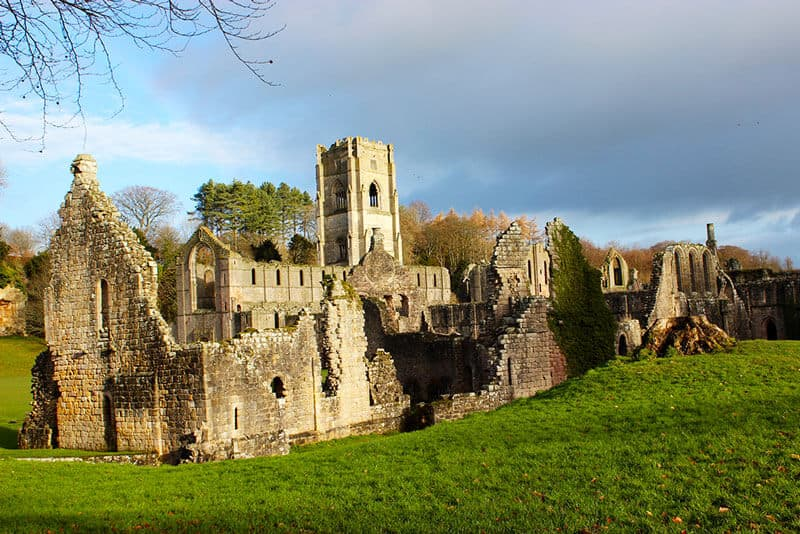 Ruins of Fountain Abbey basked in sunlight sitting in bright green grass