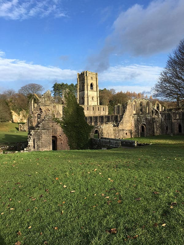 Ruins of Fountains Abbey on a crisp Autumn day. Sitting in a field of green grass with a blue sky in the background.
