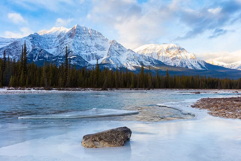 Jasper National Park in the winter. Snow capped mountains behind a flowing tree lined icy river.