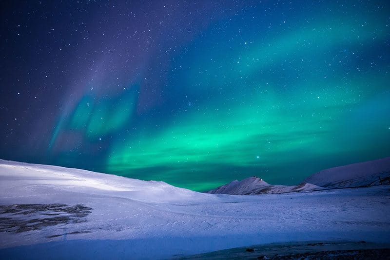 Northern Lights or the Aurora Borealis shining bright green in a dark sky with a mountain in the back ground.