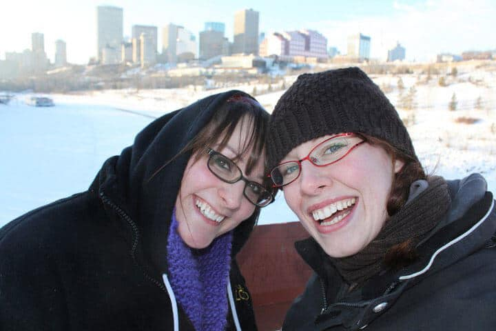 Two women standing with the Edmonton skyline in the back ground in the winter.