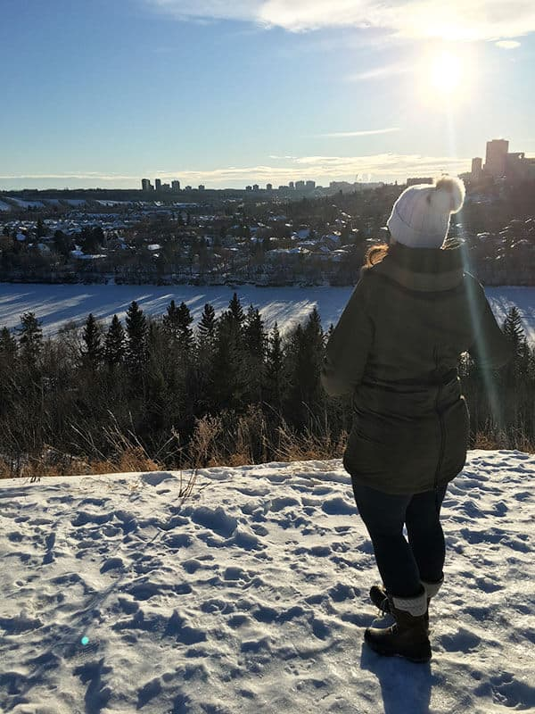 A woman looking at the view of Edmonton Skyline from the River Valley and the Frozen North Saskatchewan River in Edmonton in the winter. One of the fun things to do in Edmonton in the winter.