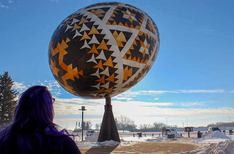 Woman looking at the giant Ukrainian Easter Egg in Vegreville. Giant Roadside Attraction. Giant Pysanka. In Alberta Canada.