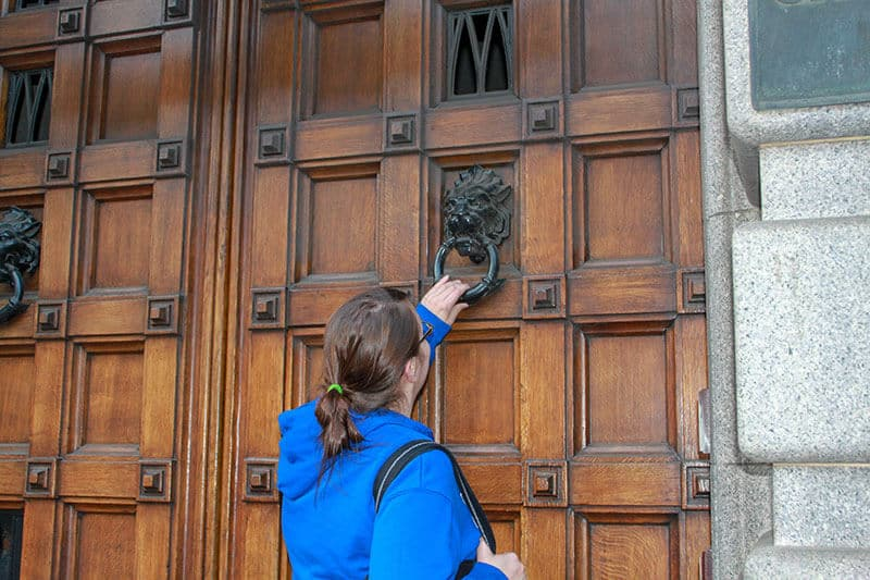 Crystal in blue hoodie knocking a large wooden door in Edinburgh