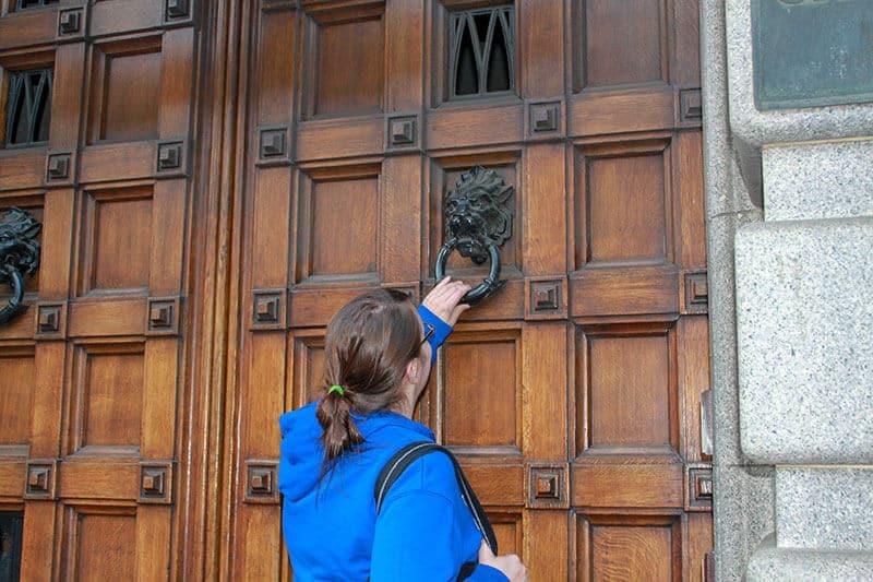 Crystal in blue hoodie knocking a large wooden door in Edinburgh