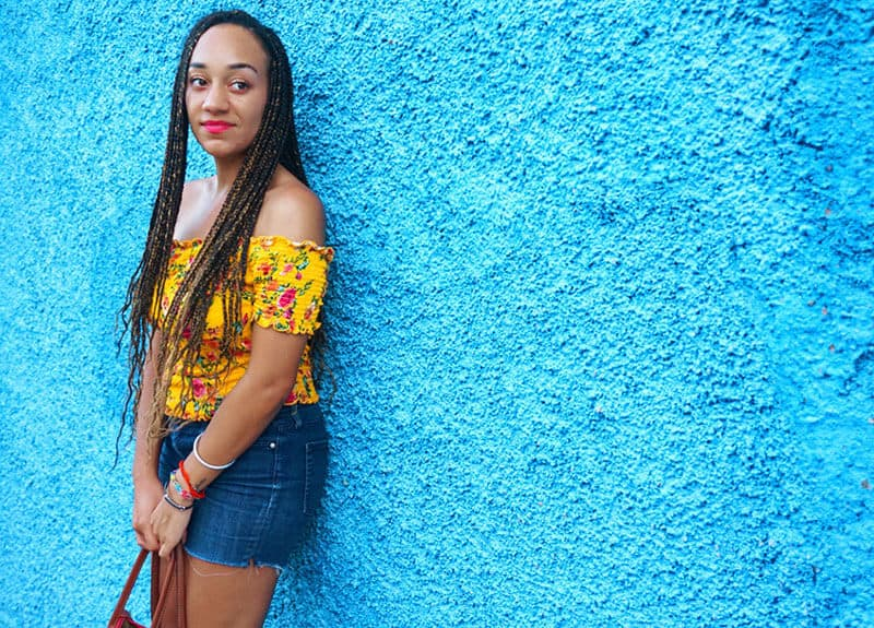 Christelle from Stella's Out in front of a vibrant blue wall