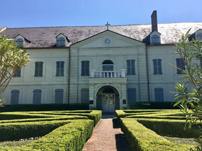The Ursuline Convent Museum in New Orleans. A red brick path with green bushes on either side leading to a large white building.