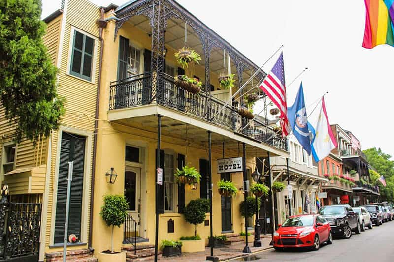 The incredibly haunted Andrew Jackson Hotel in New Orleans. A yellow colonial style building with several flags hanging from the upstairs balcony. One of the spooky sites in New Orleans.