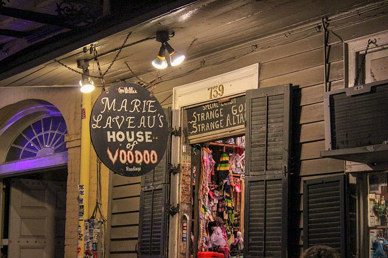 Outside of Marie Laveau's House of Voodoo at night in New Orleans. A Black building with black shutters. The door is open leading to the spooky New Orleans site of Marie Laveau's.