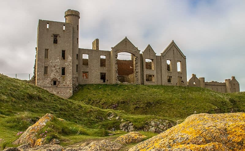 Abandoned New Slains Castle amoung the green grounds in Scotland