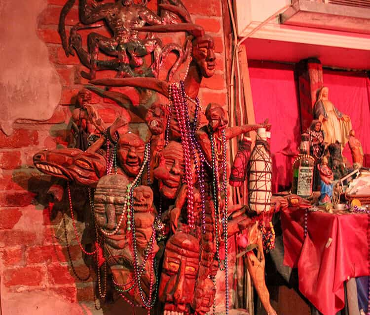 Red room filled with voodoo relics, statues and dolls in the New Orleans museum of Voodoo. One of New Orleans Spooky Sites you must visit.