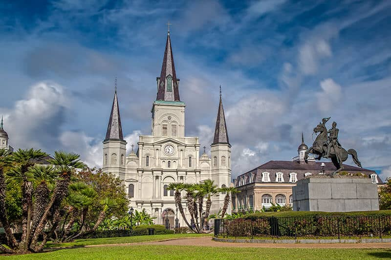 St. Louis Cathedral in the French Quarter - Huge white cathedral with three black pillars on the roof. A Statue of a man on a horse is on the right side of the photo. St. Louis Cathedral is known for being haunted and one of New Orleans Spooky Sites.