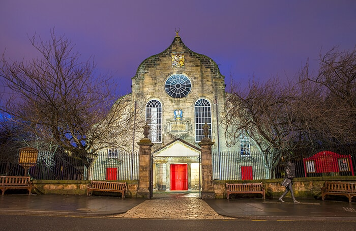 Canongate Kirk in Edinburgh at night. Bright red doors light up the large building on the Royal Mile.