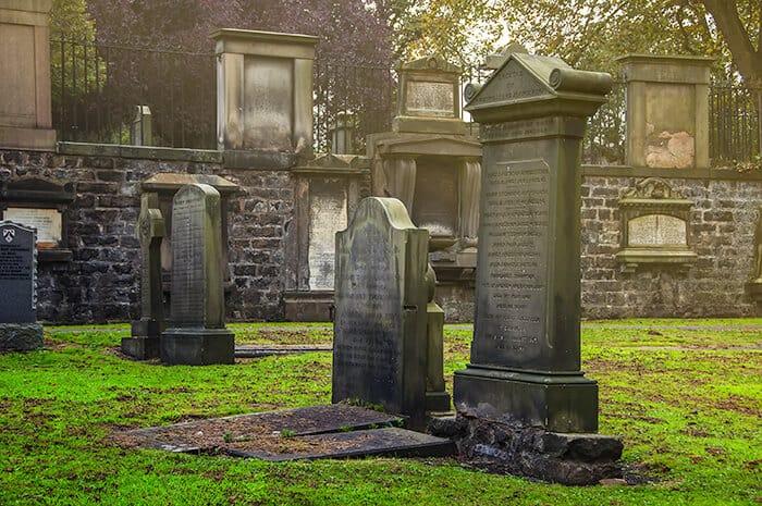Mossy green weathered headstones in Greyfrairs Graveyard