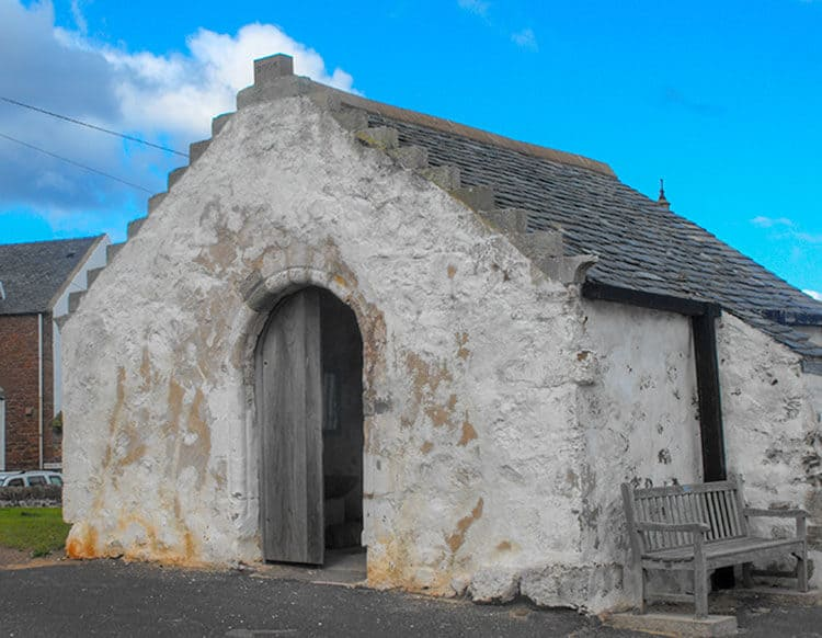 St. Andrews Old Kirk in North Berwick - Old white building with steeped roof, open door.