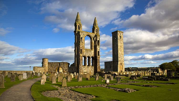 St. Andrews Cathedral in St. Andrews Scotland. Beautiful ruins towering over a grassy graveyard filled with several weathered tombstones.